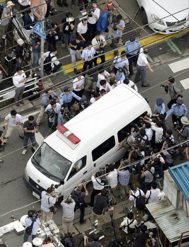 Tiedotusvälineet piirittivät ajoneuvoa, jolla joukkomurhaajaa kuljetettiin.