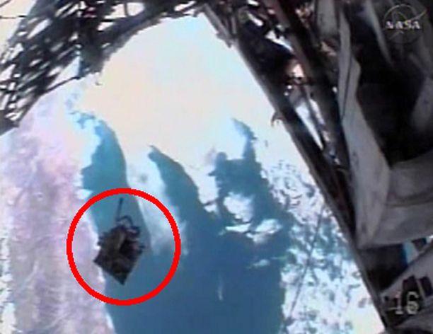 Kuva NASA-TV:n videolta, jossa näkyy kuinka työkalupakki leijuu avaruuteen. Video on kuvattu astronautin kypäräkameralla.