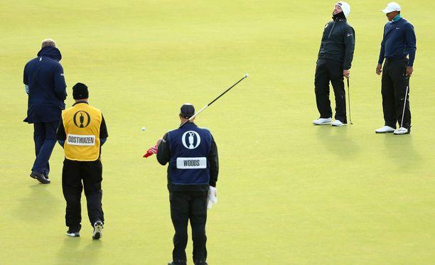 Louis Oosthuizen (toinen oikealta) ja Tiger Woods (oikealla) eivät voineet kuin nauraa, kun tuuli vei heidän pallonsa kauemmas reiästä.