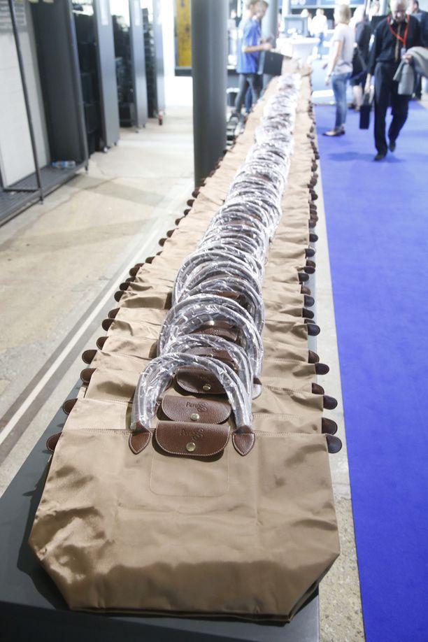 Naisille on teetetty Longchamp-merkkilaukkua muistuttava kassi, jonka etuläppää koristaa PerusS-logo.