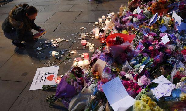 Ihmiset toivat kukkia ja kynttilöitä Manchesterissa lähelle paikkaa, jossa terrori-iskun uhrit kuolivat.