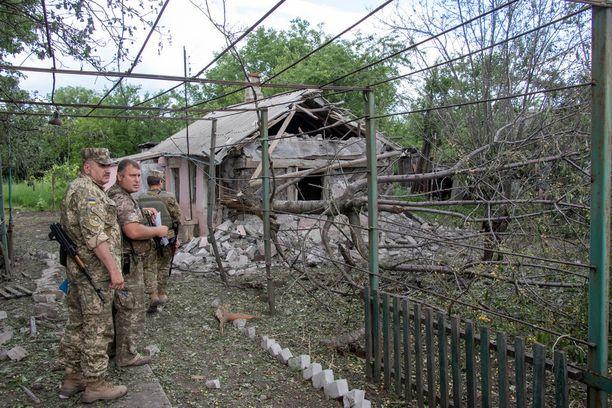 Ukrainan armeijan sotilaat tutkivat vaurioituneen talon ympäristöä lähellä etulinjaa Donetskin alueella kesäkuussa. Kuvituskuva.
