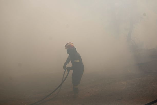 Palomies sammuttaa paloa Makrimallin kylässä.