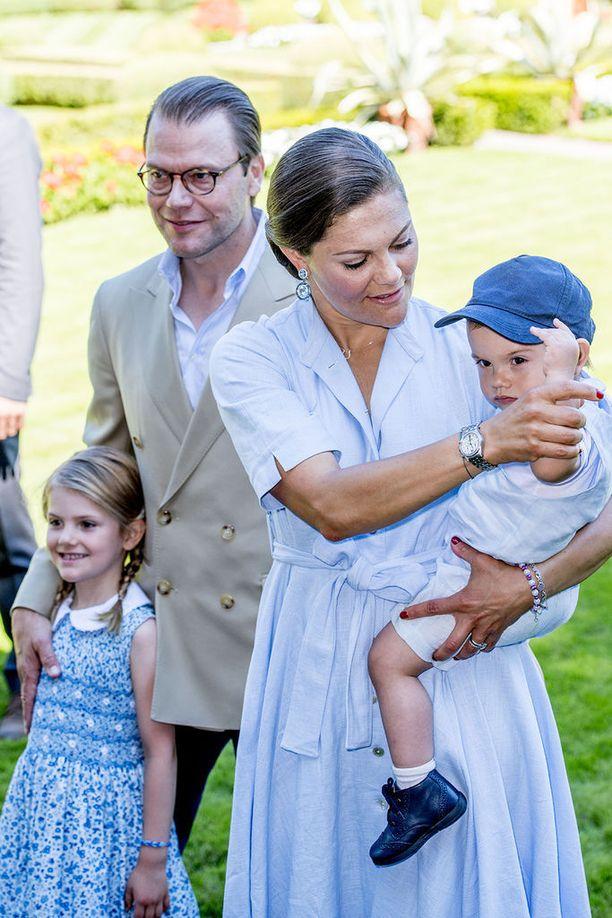 Ruotsin kruununprinsessa Victoria sylissään vakavailmeinen prinssi Oscar. Taustalla Victorian puoliso prinssi Daniel käsi prinsessa Estellen harteilla.