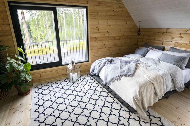 Hirsikodin yläkerrassa sijaitsevan makuuhuoneen ikkunasta avautuu näkymä järvelle. Harmaan eri sävyt luovat rauhallisen tunnelman. Asuntomessukohde 10.