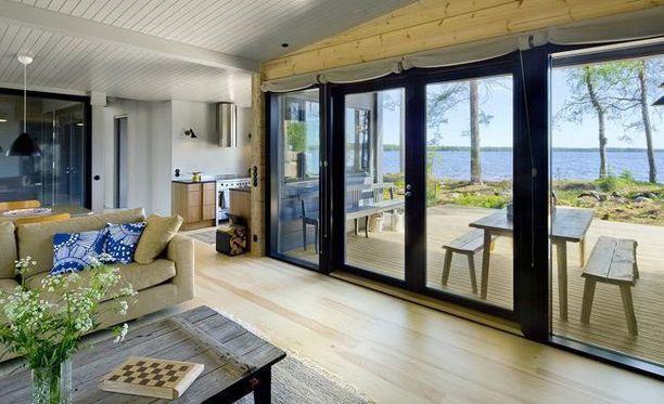 Hirsihuvila järven rannalla. Suuret ikkunat ja pariovet yhdistävät sisä- ja ulkotilat toisiinsa. Ajattoman ja selkeän tunnelman taloon on luonut sisustusuunnittelija Hanni Koroma.