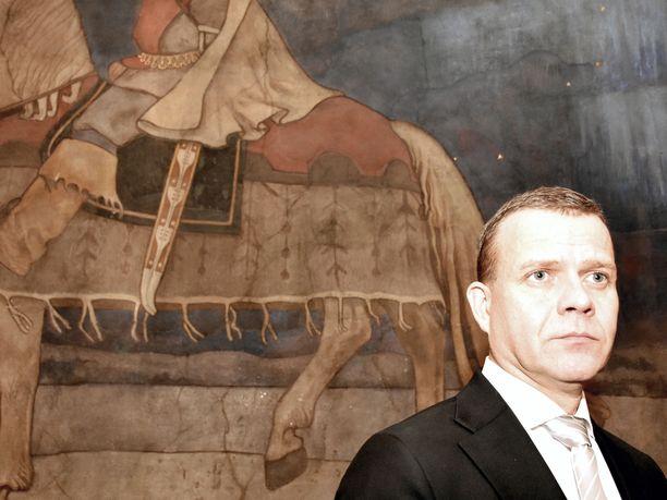 """Kokoomuksen puheenjohtaja Petteri Orpo vetoaa muihin puheenjohtajiin, että keskusteluilmapiiri ei muuttuisi nykyistä repivämmäksi, vaikka eduskuntavaalit lähestyvätkin. Orpon taustalla Akseli Gallen-Kallelan maalaus """"Kullervon sotaanlähtö"""" Vanhan ylioppilastalon musiikkisalissa."""