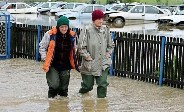 Kaksi naista kävelevät tulva-alueen läpi Pozegassa, joka on noin 200 kilometriä Serbian Belgradista lounaaseen.