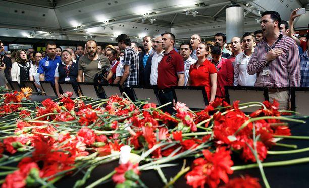 Lukuisat ihmiset osallistuivat lentokentällä terrori-iskun uhrien muistoksi järjestettyyn tilaisuuteen.