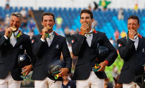 Kenttäratsastuksen joukkuekilpailun voittanut Ranskan tiimi poseerasi mitalit suussaan.