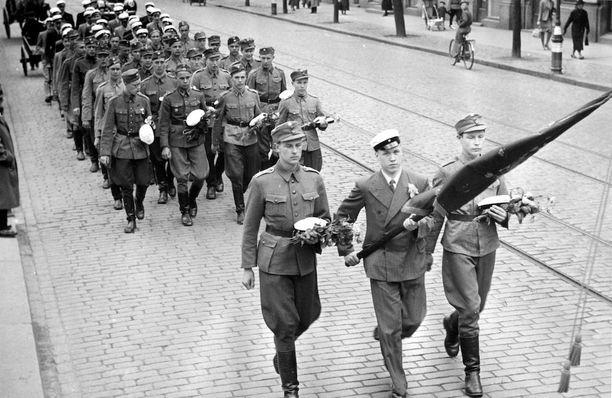 Sota-aika näkyi myös lakkiaisissa. Monet nuoret olivat menettäneet luokkatovereitaan taisteluissa. Lakkiaispäivänä olikin tuoreilla ylioppilailla tapana viedä saadut ruusut sankarihaudoille. Kuvassa on Suomalaisen normaalilyseon vastavalmistuneita ylioppilaita toukokuussa 1942.