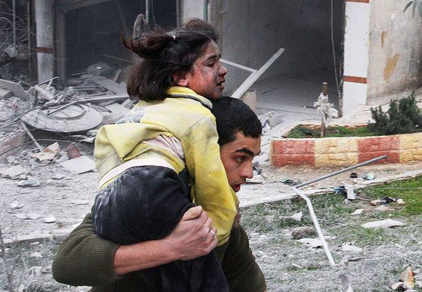 Syyrialaismies kantoi turvaan ilmapommituksissa loukkaantunutta tyttöä Aleppossa keskiviikkona.