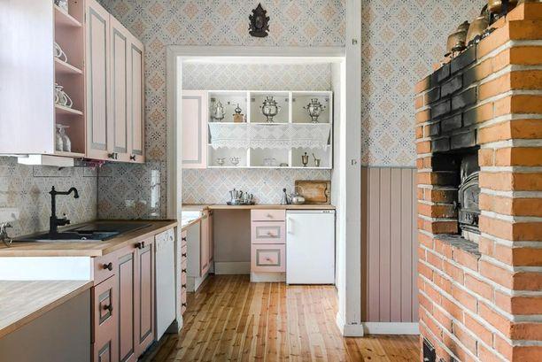 Tämän empiretyylisen kartanon keittiöstä on tehty hempeän pinkki. Seinillä ruotsalainen Duron gammalsvenska -tapetti.
