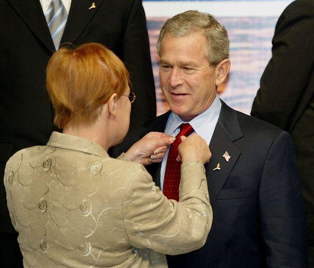 Tarja Halonen on Suomen edellinen presidentti, joka sai kutsun Valkoiseen taloon. Tässä kuvassa hän korjaa Yhdysvaltain entisen presidentin George W. Bushin solmiota Nato-huippukokouksessa vuonna 2004.