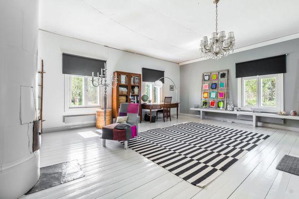 Kodin sisätilat ovat iso yllätys. Asunto on sisältä remontoitu moderniksi. Tämä sali toimittaa nykyisin valtavan makuuhuoneen virkaa. Sänky ei näy kuvassa, mutta se on oikealla seinällä. Iso, mustavalkoinen matto sitoo sisustuksen yhteen.