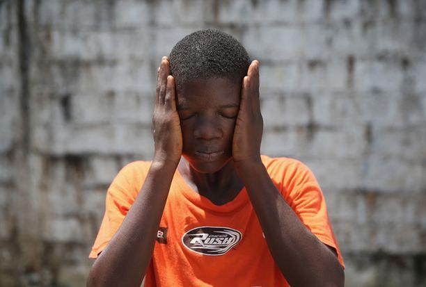 Jeremra Cooper, 16, pyyhkii kasvojaan tukahduttavassa kuumuudessa. Cooper menetti kuusi perheenjäsentään ennen kuin sairastui itse. Toipuminen kesti kuukauden.