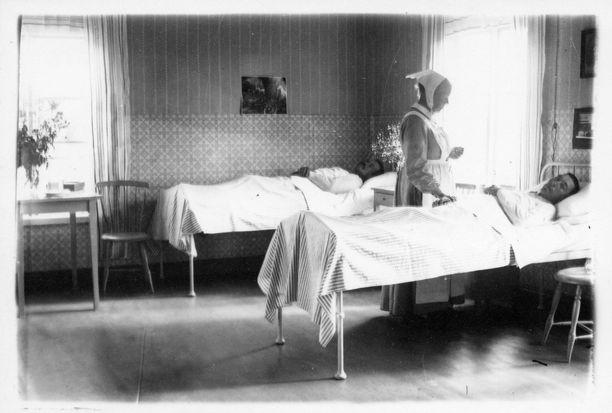 Kuvassa vuosina 1910-30 toimineen Vörån parantolan potilashuone. jossa sairaanhoitaja Paapanen hoitaa tuberkuloosiin sairastunutta potilasta.