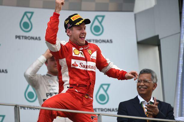 Sebastian Vettel juhli villisti ensimmäistä voittoaan Ferrarin haalareissa Malesiassa 2015.