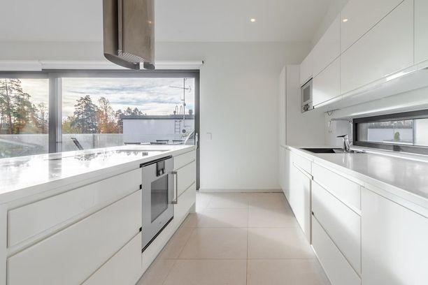 Valkoinen Puustellin keittiö on minimalistista tyyliä. Keittiössä on Gaggenaun laitteet, jotka on integroitu kaapistoihin.