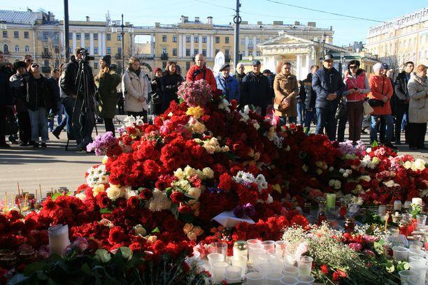 Ihmiset surevat metropommin uhreja Pietarissa huhtikuussa. Pilasoitot pommeista lisääntyivät keväisen metroiskun jälkeen.