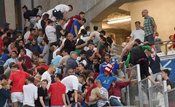 Tuhannet katsojat pakenivat Venäjän kannattajien hyökkäystä kiipeämällä turva-aitojen yli.