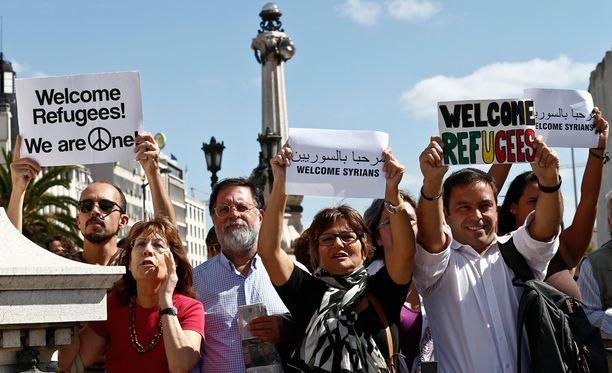 Ihmiset toivottavat turvapaikanhakijat tervetulleiksi Portugalin pääkaupungissa Lissabonissa.