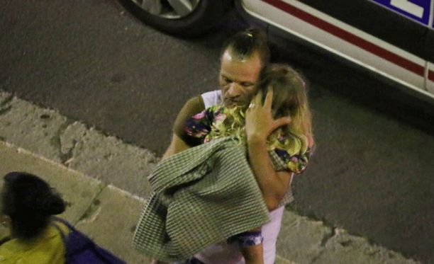Mies piteli sylissään pientä lasta iskun jälkeen Nizzassa.