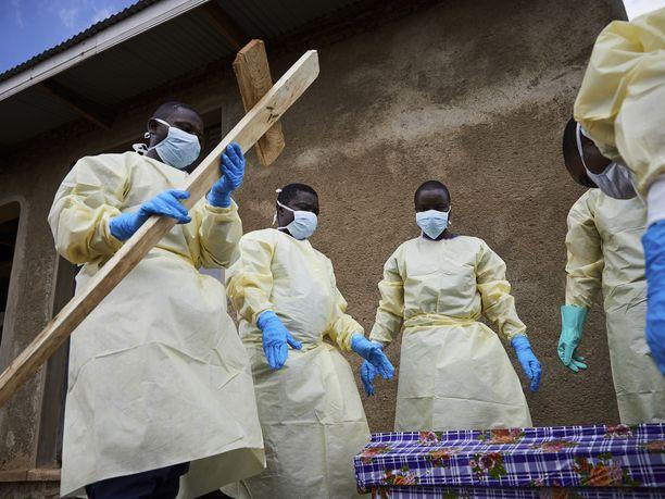 Terveystyöntekijöitä osallistuu ebolaan kuolleen ihmisen hautajaisiin Kongossa Mutwangan kylässä toukokuussa 2019.