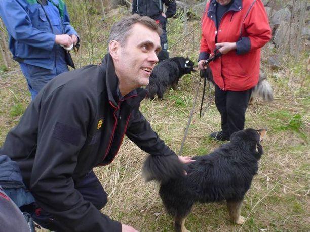 Palomies Pekka Isoaho silittelee onnellista koiraa.