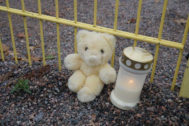 Tapahtumapaikalle on tuotu kynttilä ja nallekarhu.