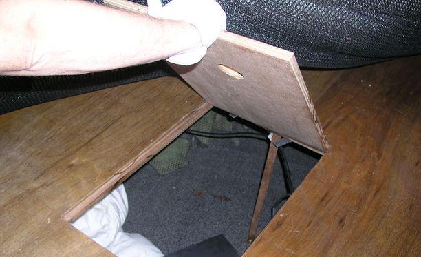 Veneen maton alla lattiassa oleva luukku, jonka alla maahantuodut piilottelivat.