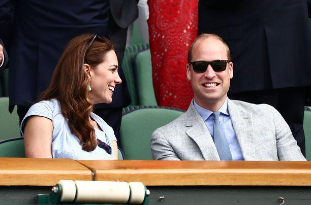 Herttuatar Catherine ja prinssi William hymyilivät toisilleen Wimbledonin katsomossa.