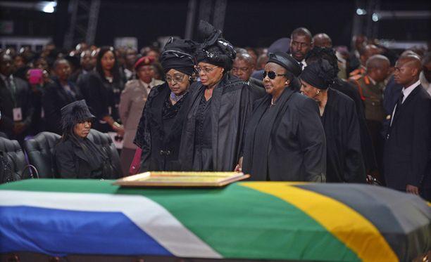 Nelson Mandelan leski Graca Machel (kesk. )ja ex-vaimo Winnie Mandela Madikizela (vas.) seisoivat Mandelan arkun äärellä hautajaisseremonian aikana.