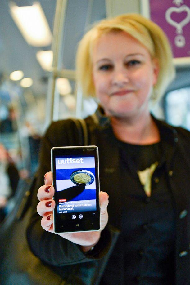 Niina, 43, lukee junassa uutisia. Ilmaisjakelulehti on joutunut väistymään puhelimen tieltä.