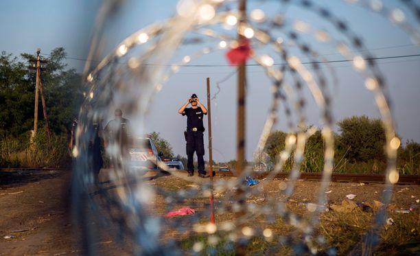 Unkarilainen poliisi tarkkailee kiikareilla Unkarin ja Serbian välistä rajaa. Pakolaiskriisi uhkaa sulkea rajat Euroopan sisällä.