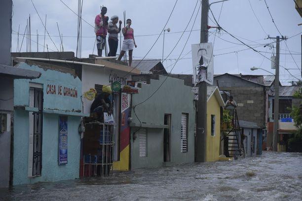 Tulvavesiä paenneet ihmiset odottivat evakuointia kotiensa katolla Dominikaanisessa tasavallassa.