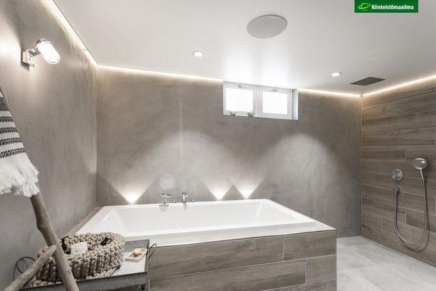 Tässä harmaassa ja muotoilultaan yksinkertaisessa kylpyhuoneessa on tunnelmavalaistus kohdillaan.