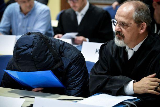 Syytetyt peittivät kasvonsa oikeudessa.