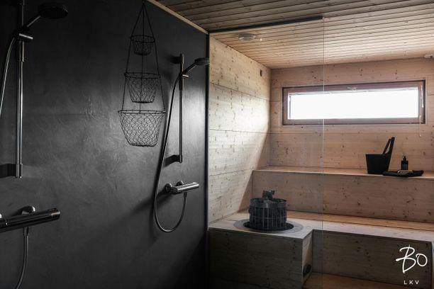 Kuusiverhoiltu sauna on pelkistetty. Tummat suihkuseinät tuovat kauniin kontrastin tilaan. Suihkusaippuoita varten laitetut metallikorut roikkuvat hauskasti katosta.