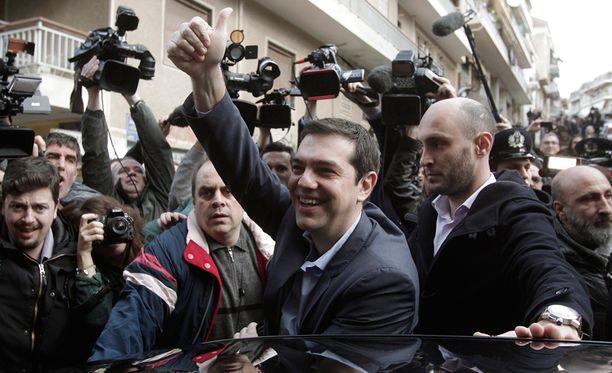 Vasemmistopuolue Syrizan puheenjohtaja Alexis Tsipras riemuitsi ovensuukyselyiden tuloksista.