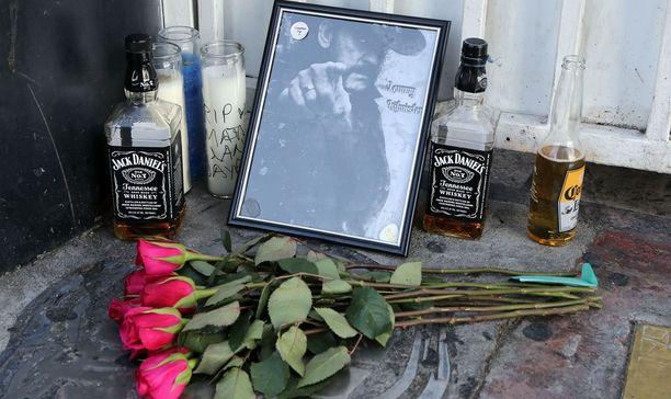 Fanit ovat tuoneet baarin eteen viskiä ja punaisia ruusuja.