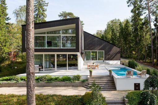 Espoon Suvisaaristossa sijaitsevan talon terassilla on tilaa myös uima-altaalle. Lasiovet yhdistävät terassin ja olohuoneen.