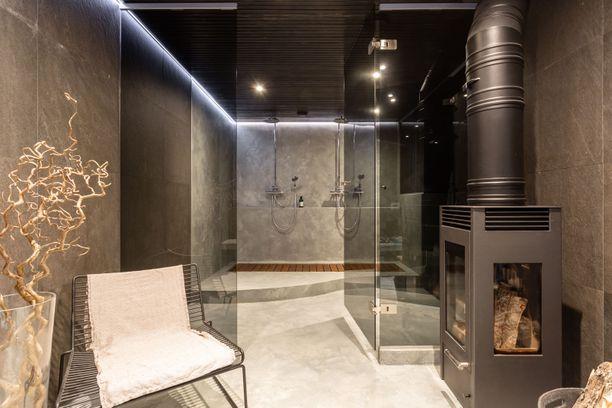 Kellarikerroksen saunaosaston pesutiloissa on tummaa, trendikästä värimaailmaa.