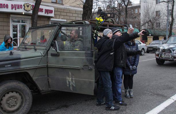 Paikalliset nuoret ottivat selfieitä yhdessä Azov-pataljoonan taisteluista palanneiden sotilaiden kanssa Mariupolissa keskiviikkona.