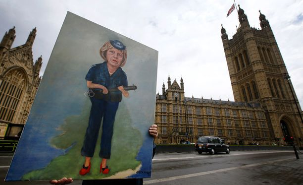 Taiteilija Kaya Mar kantoi Theresa Mayta esittävää maalaustaan parlamenttitalon lähistöllä tiistaina.
