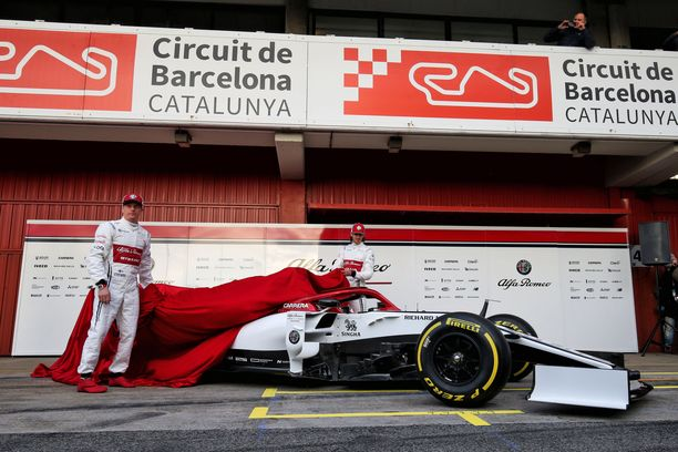 Kimi Räikkönen (vas.) ja Antonio Giovinazzi repivät peitteet uuden Alfa Romeon päältä pois.