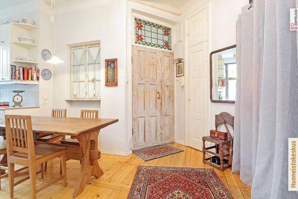 Joulutähdet oven yläpuolella olevassa lyijylasi-ikkunassa toivottavat tervetulleeksi kaksioon Helsingin Kampissa.