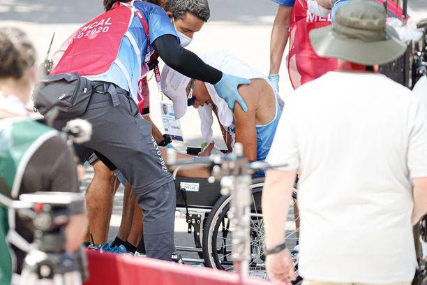 Toimitsijat nostivat Aleksi Ojalan pyörätuoliin 50 kilometrin kävelykisan jälkeen.