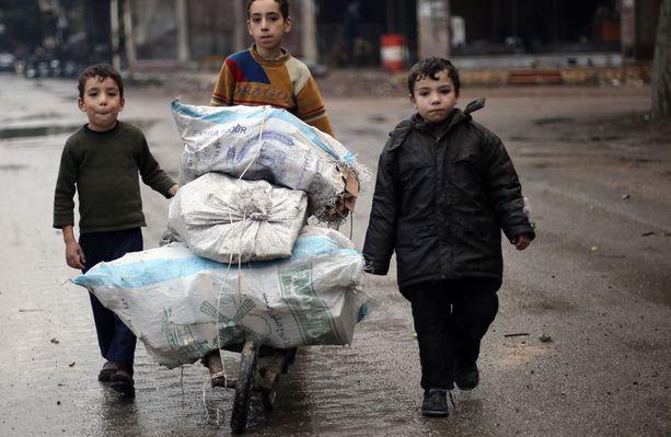 Lapset keräävät tuhotuista rakennuksista huonekaluja polttopuiksi.