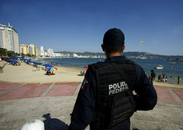 Tuttu näky nyky-Acapulcossa: aseistettu poliisi vartioi uimarantaa.